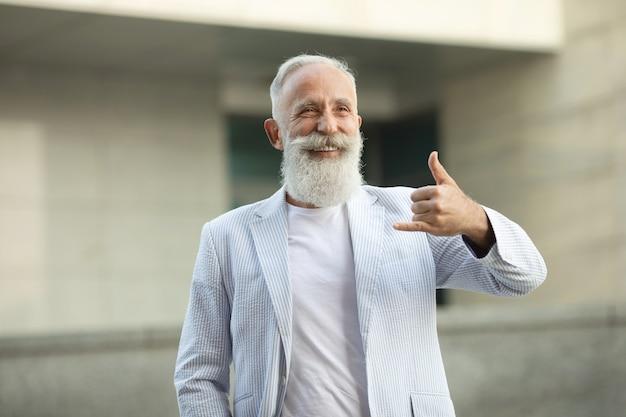 Älterer bartmann, der telefonzeichen tut Premium Fotos