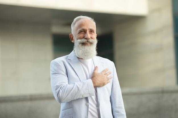 Älterer bartmann mit der hand auf seiner brust Premium Fotos