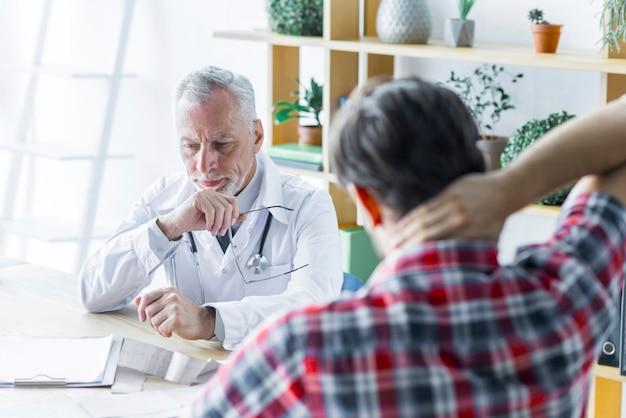 Älterer doktor, der bei der unterhaltung mit patienten denkt Kostenlose Fotos