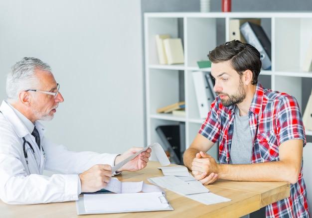 Älterer doktor, der mit patienten im büro spricht Kostenlose Fotos