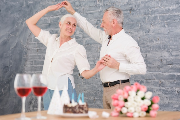 Älterer ehemann und frau, die an der geburtstagsfeier tanzt Kostenlose Fotos