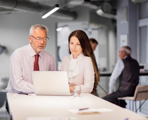 Älterer geschäftsmann und geschäftsfrau, die laptop im büro betrachtet Kostenlose Fotos
