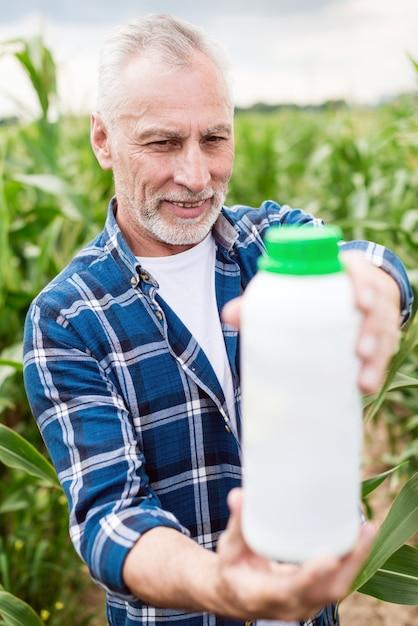 Älterer landwirt, der auf einem gebiet schaut auf einer flasche mit mineraldüngern steht. Premium Fotos