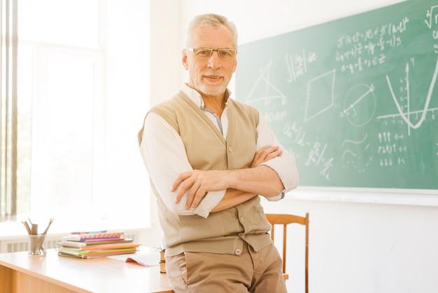 Älterer lehrer, der nahen schreibtisch im klassenzimmer steht Premium Fotos
