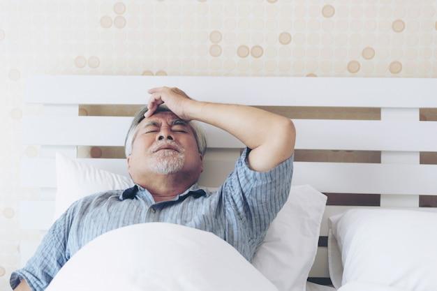 Älterer männlicher asiat, der zu hause unter den schlimmen schmerz in seinem kastenherzangriff leidet Premium Fotos