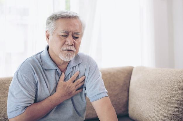 Älterer männlicher asiat, der zu hause unter schlechten schmerz in seinem kastenherzinfarkt - älteres herz leidet Premium Fotos
