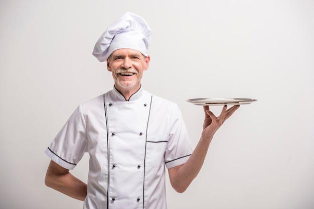Älterer männlicher hauptkoch im einheitlichen haltenen behälter. Premium Fotos
