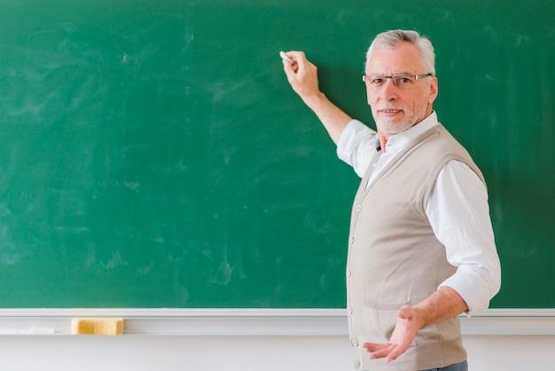 Älterer männlicher professor, der auf grüne tafel erklärt und schreibt Kostenlose Fotos