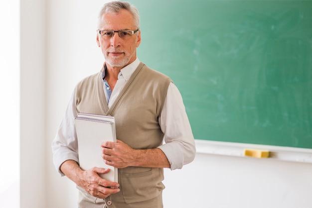 Älterer männlicher professor in den gläsern, die das notizbuch steht gegen tafel halten Kostenlose Fotos