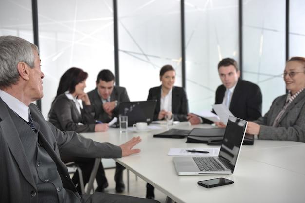 Älterer männlicher sprecher, der eine darstellung bei einem geschäftstreffen im büro gibt Premium Fotos