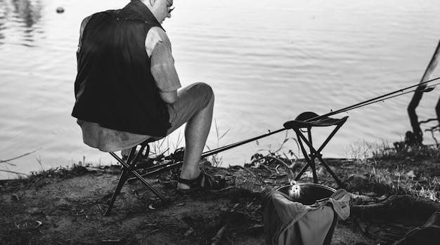 Älterer mann beim angeln an einem see Kostenlose Fotos