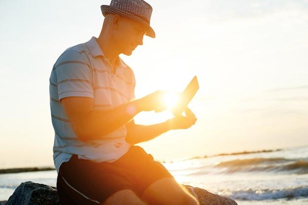 Älterer mann, der an seinem laptop auf dem strand während des sonnenuntergangs arbeitet Premium Fotos