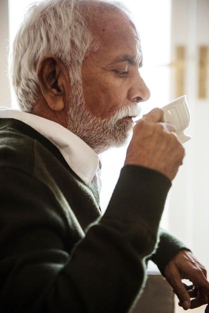 Älterer mann, der an tee nippt und trinkt Kostenlose Fotos