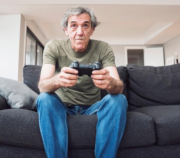 Älterer mann, der auf dem sofa spielt videospiel mit steuerknüppel sitzt Kostenlose Fotos