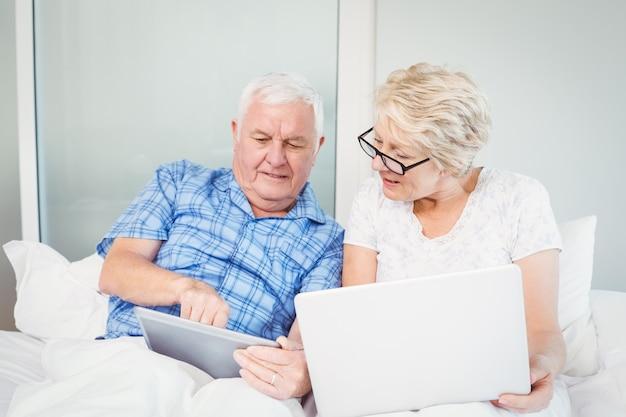 Älterer mann, der auf tablette mit frau zeigt Premium Fotos