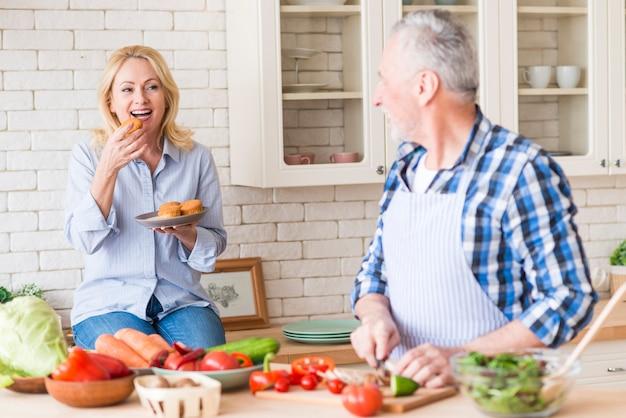 Älterer mann, der das gemüse auf dem hackenden brett betrachtet ihre frau isst die muffins in der küche schneidet Kostenlose Fotos