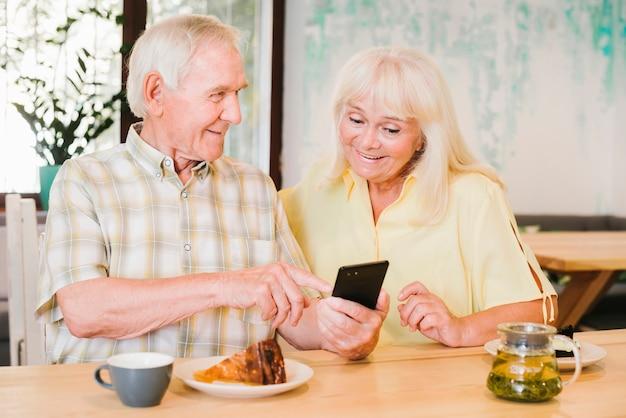 Älterer mann, der der frau smartphone zeigt Kostenlose Fotos
