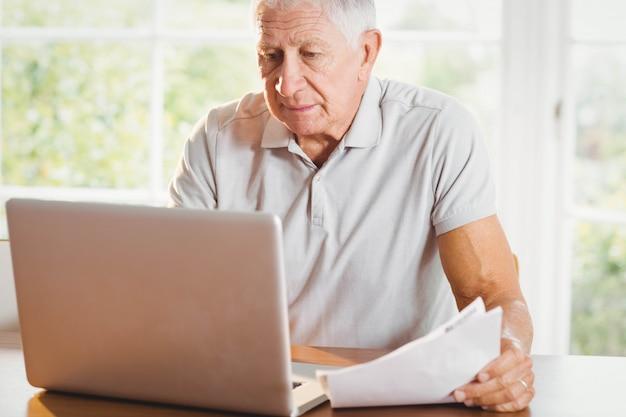 Älterer mann, der dokumente verwahrt und zu hause laptop verwendet Premium Fotos