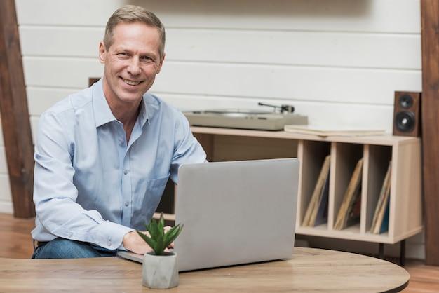 Älterer mann, der durch das internet auf seinem laptop schaut Kostenlose Fotos