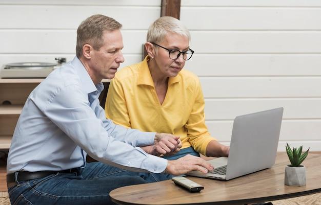 Älterer mann, der durch seinen laptop nahe bei seiner frau schaut Kostenlose Fotos