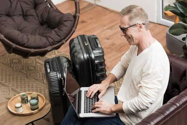 Älterer mann, der durch seinen laptop schaut Kostenlose Fotos