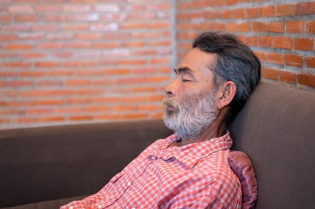 Älterer mann, der ein nickerchen im sofa zu hause macht. Premium Fotos