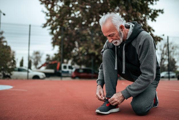 Älterer mann, der für einen lauf auf stadion im freien sich vorbereitet. Premium Fotos