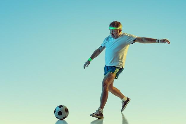 Älterer mann, der fußball in sportbekleidung auf farbverlauf und neonlicht spielt Kostenlose Fotos