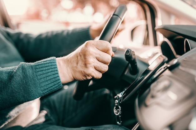 Älterer mann, der hände am lenken hält, während und sein auto fährt. Premium Fotos