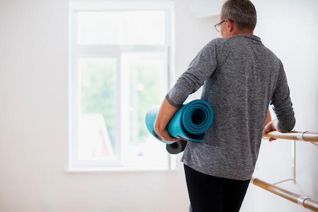 Älterer mann der hinteren ansicht, der yogamatte hält Kostenlose Fotos