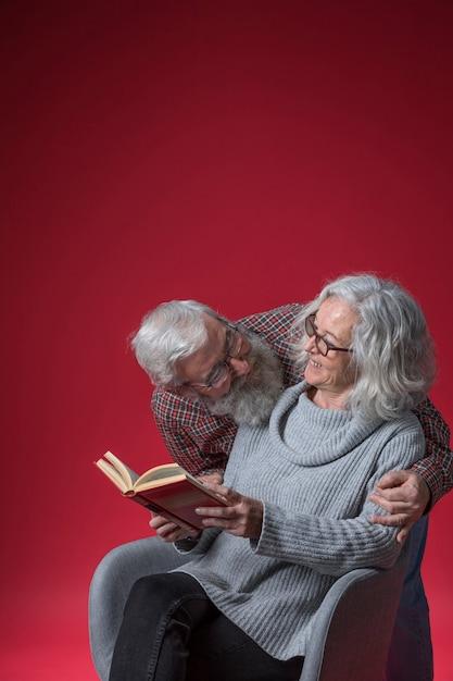 Älterer mann, der ihre frau sitzt auf dem stuhl liest das buch gegen roten hintergrund liebt Kostenlose Fotos