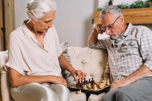 Älterer mann, der ihre frau spielt schach betrachtet Kostenlose Fotos