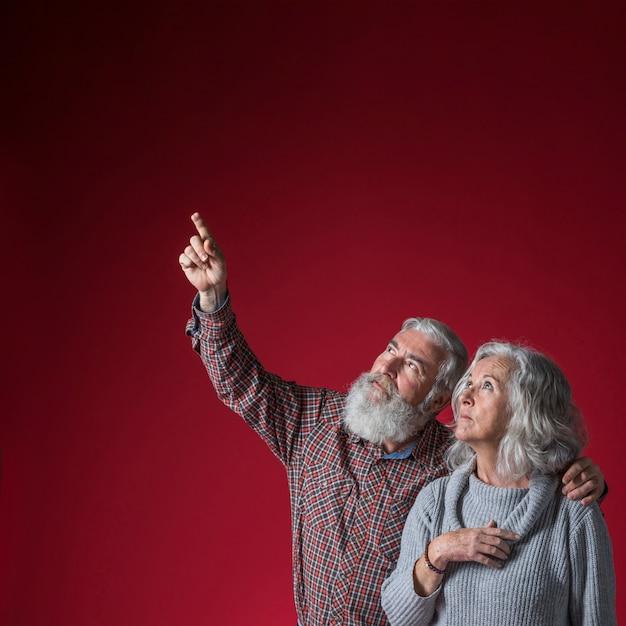 Älterer mann, der ihren ehemann zeigt aufwärts etwas gegen roten hintergrund betrachtet Kostenlose Fotos