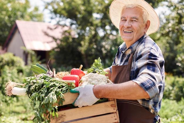 Älterer mann, der im feld mit blumen arbeitet Kostenlose Fotos