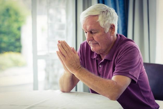 Älterer mann, der im wohnzimmer betet Premium Fotos