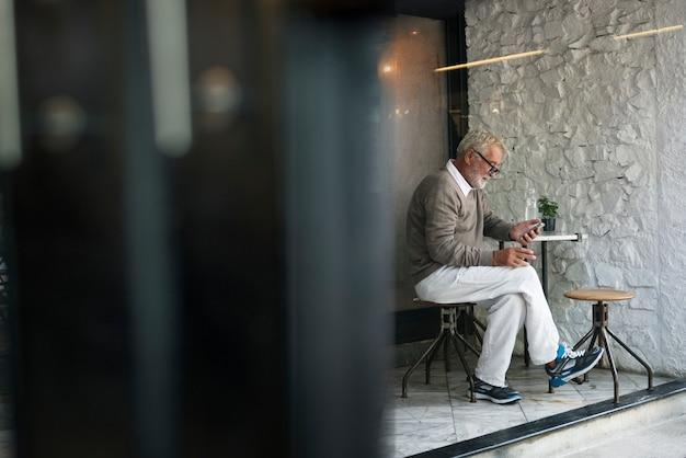 Älterer mann, der intelligentes telefon-verbindungs-konzept verwendet Premium Fotos