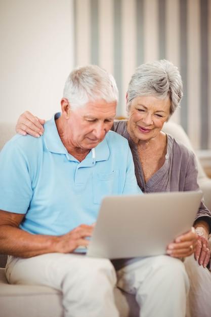 Älterer mann, der mit frau auf sofa sitzt und laptop im wohnzimmer verwendet Premium Fotos