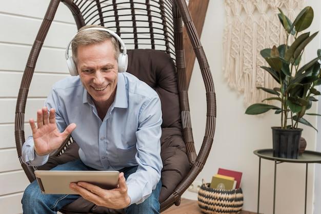 Älterer mann, der mit seinen kindern durch eine tablette spricht Kostenlose Fotos