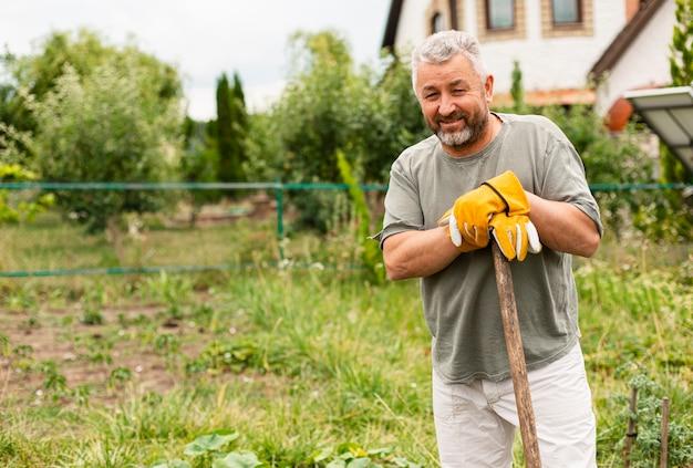 Älterer mann der vorderansicht im garten Kostenlose Fotos
