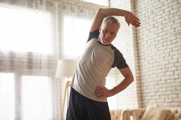 Älterer mann, der zu hause einfaches training ausdehnt. Premium Fotos