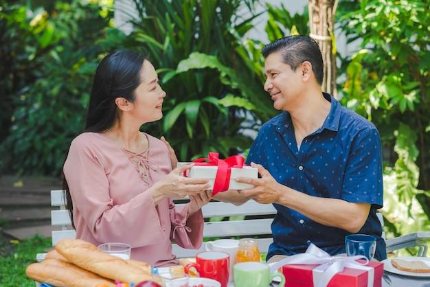 Älterer mann des glücklichen paars, der seiner frau giftbox beim frühstück zusammen zu hause garde gibt Premium Fotos