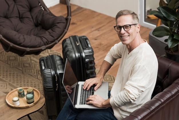 Älterer mann des hohen winkels, der durch seinen laptop schaut Kostenlose Fotos