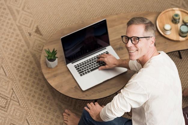 Älterer mann des hohen winkels, der einen laptop verwendet Kostenlose Fotos