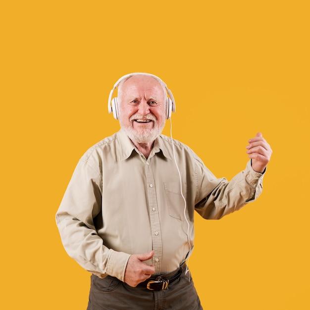 Älterer mann des smiley, der eingebildeten quitar spielt Kostenlose Fotos