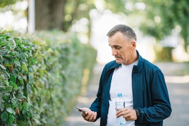 Älterer mann im freien, der mobile betrachtet Kostenlose Fotos