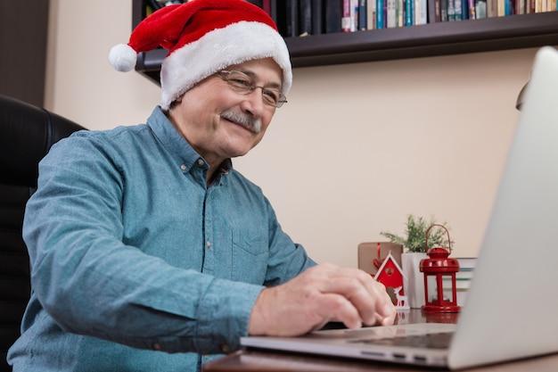 Älterer mann im weihnachtsmannhut spricht unter verwendung des laptop-geräts für videoanruffreunde und -kinder. das zimmer ist festlich eingerichtet. Premium Fotos