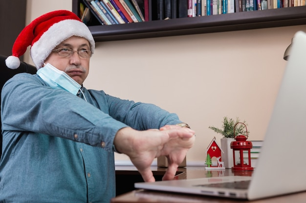 Älterer mann im weihnachtsmannhut spricht unter verwendung des laptops für videoanruffreunde und -kinder. das zimmer ist festlich eingerichtet. weihnachten während des coronavirus. Premium Fotos