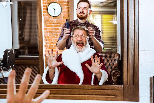 Älterer mann im weihnachtsmannkostüm, das seinen persönlichen meister im friseurladen vor weihnachten rasiert Kostenlose Fotos