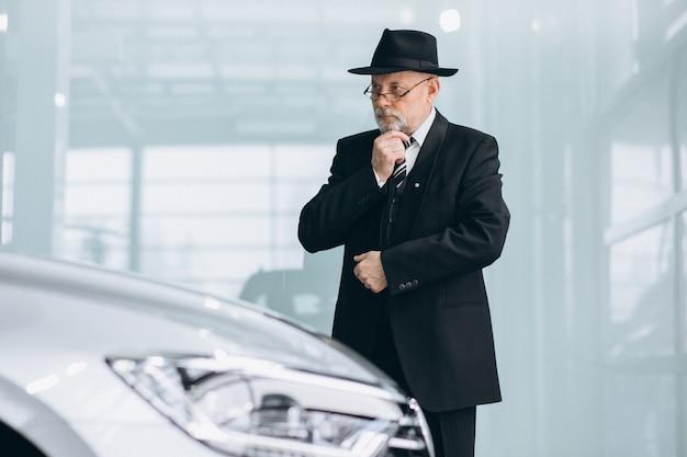 Älterer mann in einem autosalon, der ein auto wählt Kostenlose Fotos