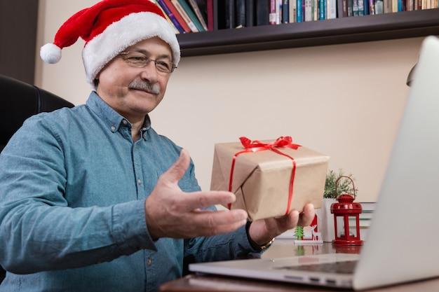 Älterer mann in weihnachtsmannhut gibt ein geschenk und spricht mit laptop-gerät für videoanruffreunde und kinder. Premium Fotos